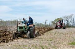 Landwirte, die mit alten Maschinen pflügen Lizenzfreie Stockfotografie