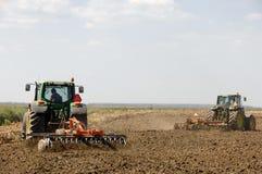 Landwirte, die mit Traktor pflügen Lizenzfreie Stockfotografie