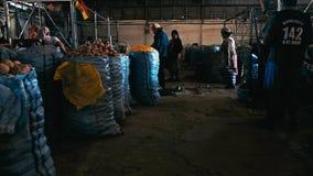 Landwirte, die nahe dem Stadtmarkt warten, um ihre Kartoffeln in den Plastiktaschen zu verkaufen stockbilder