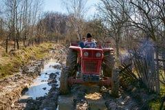 Landwirtfamilie, die einen Traktor auf einer schlammigen Landstraße fährt Stockbild