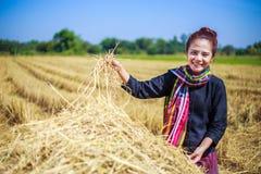 Landwirtfrau, die mit dem Stroh auf dem Gebiet sich entspannt Lizenzfreie Stockfotos