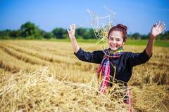 Landwirtfrau, die mit dem Stroh auf dem Gebiet sich entspannt Lizenzfreies Stockfoto