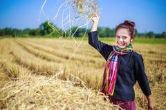 Landwirtfrau, die mit dem Stroh auf dem Gebiet sich entspannt Stockbild