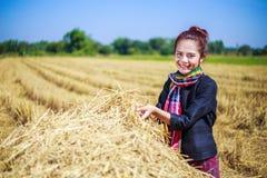 Landwirtfrau, die mit dem Stroh auf dem Gebiet sich entspannt Lizenzfreie Stockbilder