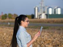Landwirtfrau mit Tablette und Silos Stockbild