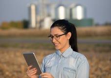 Landwirtfrau mit Tablette und Silos Lizenzfreie Stockfotos