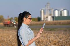 Landwirtfrau mit Tablette und Silos Stockfotos