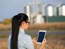 Landwirtfrau mit Tablette und Silos Stockfoto
