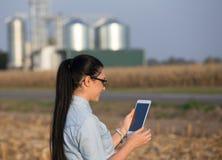 Landwirtfrau mit Tablette und Silos Stockfotografie