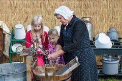 Landwirtfrau zeigt den Gebrauch von einem traditionellen washhub während eines niederländischen landwirtschaftlichen festiva Lizenzfreie Stockbilder