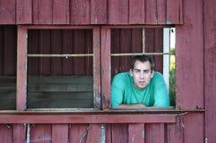 Landwirtmann, der heraus alten Stall schaut Lizenzfreies Stockfoto