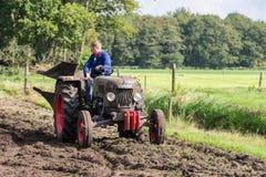 Landwirtreiten mit einem alten Traktor während eines niederländischen landwirtschaftlichen Festivals Lizenzfreies Stockfoto