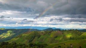Landwirtschaft auf Berg mit Regenbogen Stockfotografie