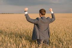 Landwirtschaft, glücklicher Landwirt, der auf dem Weizengebiet bereit, mit den Händen und dem Daumen oben zu ernten gestikuliert Stockfotos