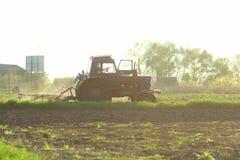 landwirtschaft Traktor, der Feld im Sonnenuntergang pflügt Bebautes Feld Agronomie, bewirtschaftend, Ackerbau Stockfotografie