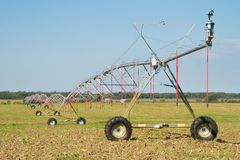 Landwirtschaft von Bewässerung mit Gelenk-Sprinkleranlage Stockfotografie