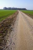 Landwirtschaftliche Kiesstraße zwischen landwirtschaftlichen Feldern Lizenzfreies Stockfoto