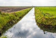 Landwirtschaftliche Landschaft diagonal geteilt durch einen Abzugsgraben Lizenzfreies Stockbild
