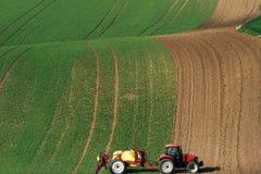 Landwirtschaftliche Landschaft mit dem Traktor, der ein gestreiftes braunes Feld pflügt Lizenzfreie Stockfotos