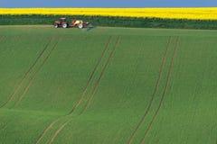Landwirtschaftliche Landschaft mit dem Traktor, der ein gestreiftes braunes Feld pflügt Stockfotos