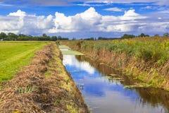 Landwirtschaftliche Landschaft mit vor kurzem ausgebaggertem Abzugsgraben in Friesland, Lizenzfreie Stockbilder