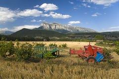 Landwirtschaftliche Maschinen auf dem Gebiet mit ausgedehnten Ansichten von Parque National de Ordesa nahe Ainsa, Huesca, Spanien Lizenzfreie Stockfotografie
