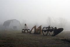 Landwirtschaftliche Maschinen auf dem nebeligen Gebiet Stockbilder