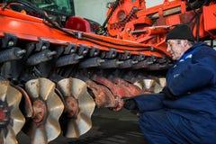 Landwirtschaftliche Maschinerie der Mechanikerreparaturen Vorbereitung der Ausrüstung für praktische Arbeit stockfotografie