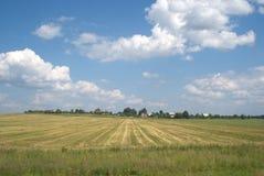 Landwirtschaftliche Sommerlandschaft mit Häusern auf Skylinen Stockfoto
