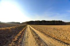 Landwirtschaftliche Straße durch die Felder Stockbilder