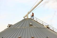 Landwirtschaftlicher amerikanischer Mann oben auf Metallkorn-Stauraum Stockfoto