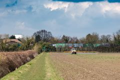 Landwirtschaftlicher Sprüher, der im Frühjahr ein chemisches Schädlingsbekämpfungsmittel auf einem Bauernhoffeld einführt stockfotografie
