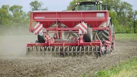 Landwirtschaftlicher Traktor mit der Anhängersämaschine, die an gepflogenem Feld arbeitet Ländliche Landwirtschaft stock footage