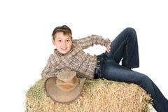 Landwirtschaftliches Kind, das auf Heuballen liegt Stockbild