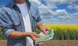 Landwirtschaftliches Konzept, Landwirt, Geld und Feld Lizenzfreies Stockfoto