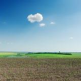 Landwirtschaftsfeld und -wolke im blauen Himmel Lizenzfreie Stockfotos