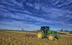 Landwirtschaftslandschaft mit dem Ackerschlepper, der den Boden vorbereitet Lizenzfreies Stockbild