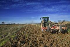 Landwirtschaftslandschaft mit dem Ackerschlepper, der den Boden vorbereitet Lizenzfreie Stockbilder