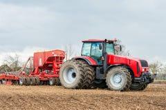 Landwirttraktor, der auf dem Gebiet arbeitet Frühlingszeit für das Säen Lizenzfreie Stockbilder