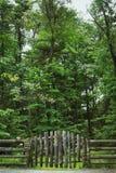 Landzaun und -zeichen mit Wald im Hintergrund Stockfotografie