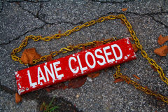 Lane Closed. Sign that has fallen to the ground on cracked asphalt Royalty Free Stock Photos