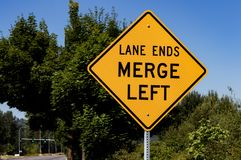 Lane ends merge left sign with trees stock photography