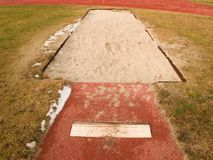 Lane for the long jump. Sandy red retrack, white ake-off board. Poor grass around Stock Images