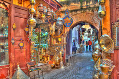 In a lane in the medina of the old Kingdom City Fes in Morocco, Africa. Ware and gifts of copper and brass are exposed for sale Royalty Free Stock Photos