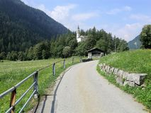 Lane towards a church in the Engadine, Switzerland Royalty Free Stock Photos