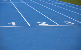 Lanes of a blue athletic track with one two and three numbers. Lanes of a blue athletic track with numbers one two and three Stock Photos