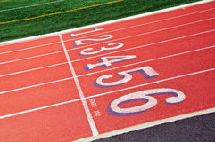 Lanes of a red race track with numbers. And green football field Royalty Free Stock Photos