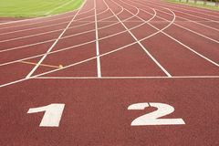 Lanes of a red race track with numbers in the stadium. stock images
