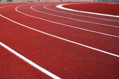 Lanes on red running track. A view of lanes and lane markings at a curve of a bright red running track royalty free stock photography
