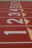 Lanes on running track. Numbered lanes on athletic running track with lane one in foreground Stock Image